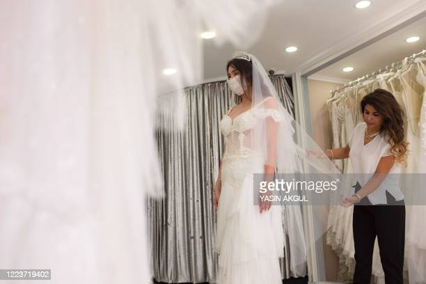 Wedding dress designer Pinar Bent adjusts a wedding dress with matching protective mask on a mannequin in her store in Istanbul on June 30 2020...