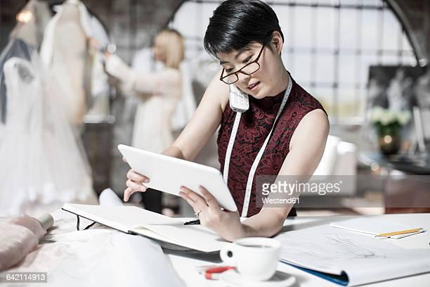 Wedding dress designer talking on phone, tablet-pc