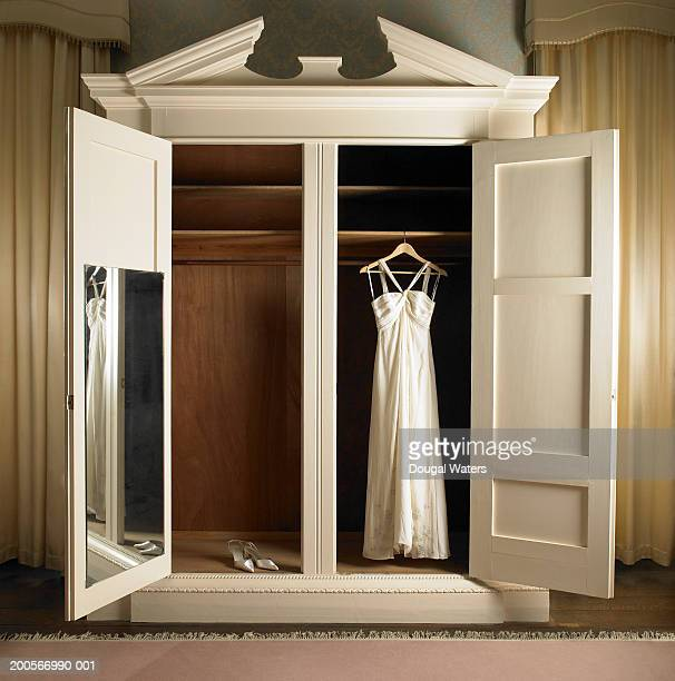 Wedding dress hanging in wardrobe with shoes
