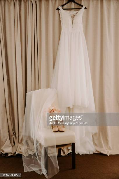wedding dress hanging on coat hanger against brown curtain - dress stock pictures, royalty-free photos & images