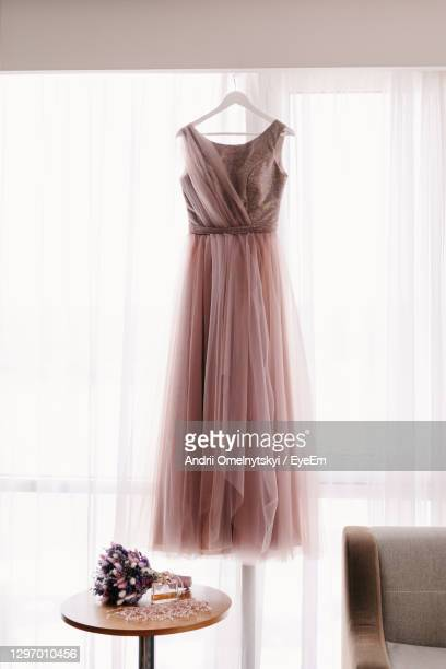 wedding dress hanging on coat hanger against white curtain - dress stock pictures, royalty-free photos & images
