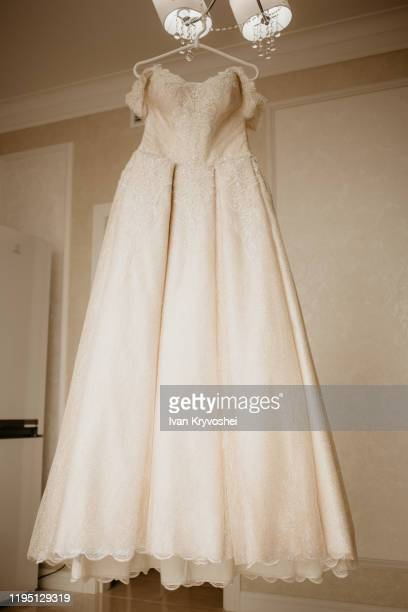 wedding dress on hanger in the bride room. on her wedding day - satin dress stock pictures, royalty-free photos & images