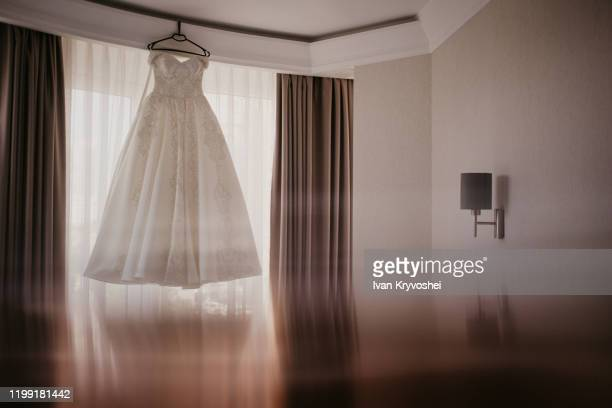 wedding dress on hanger near window in the bride room. on her wedding day. reflection on the bottom - satin dress stock pictures, royalty-free photos & images