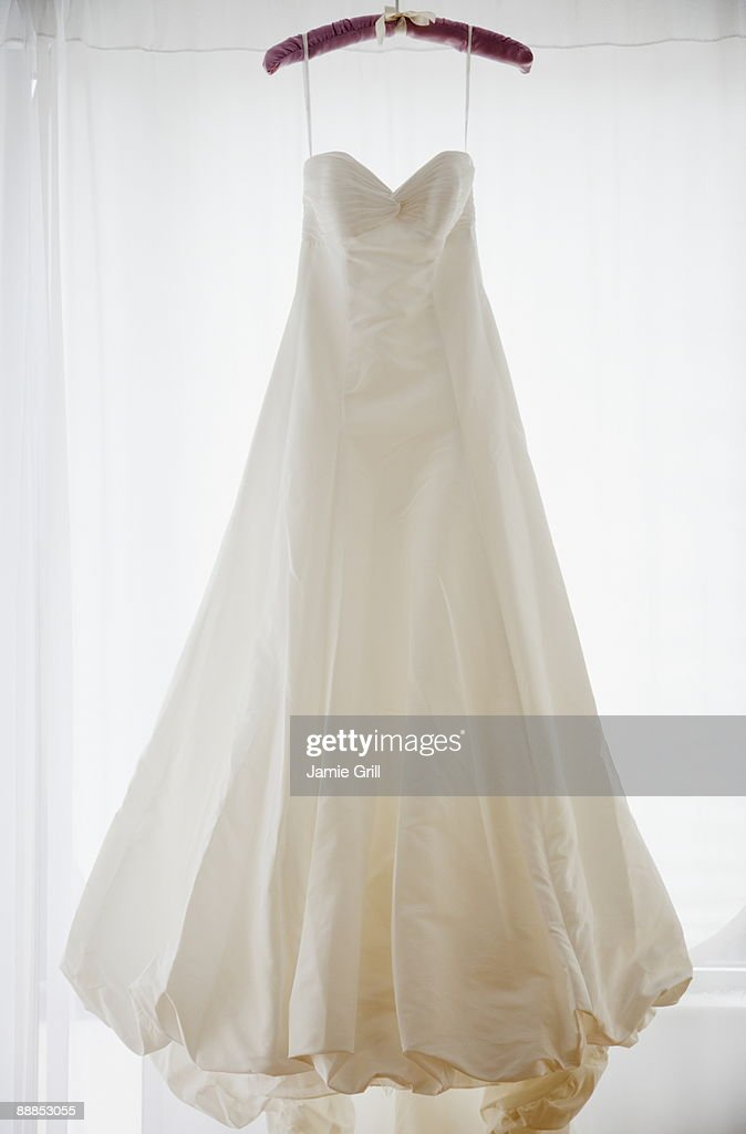 Wedding dress on hanger, studio shot : Stock Photo