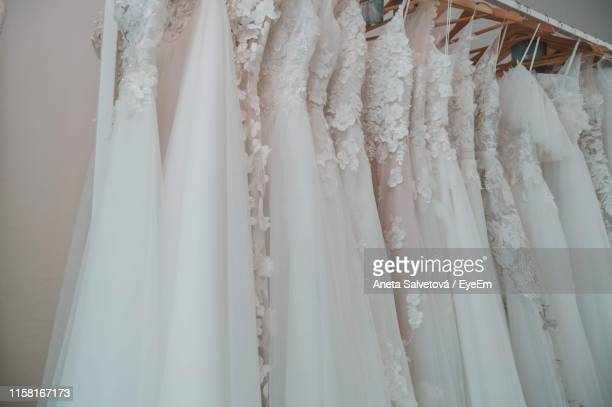 wedding dresses hanging at store - robe de mariée photos et images de collection