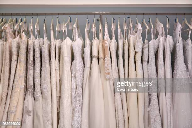 wedding dresses hanging on clothes rack at store - wedding dress stock pictures, royalty-free photos & images