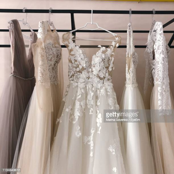 wedding dresses hanging on rack in store - lace dress stock pictures, royalty-free photos & images