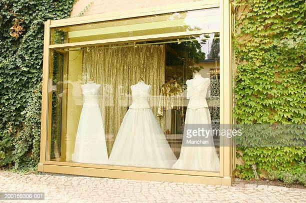 Wedding dresses on mannequins in shop window