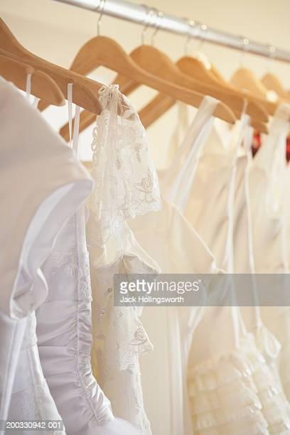 Wedding dresses on metal rack in clothing store