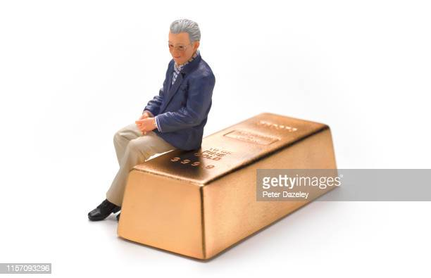 wedding figurine retired man sitting on gold bar - figurine stock pictures, royalty-free photos & images