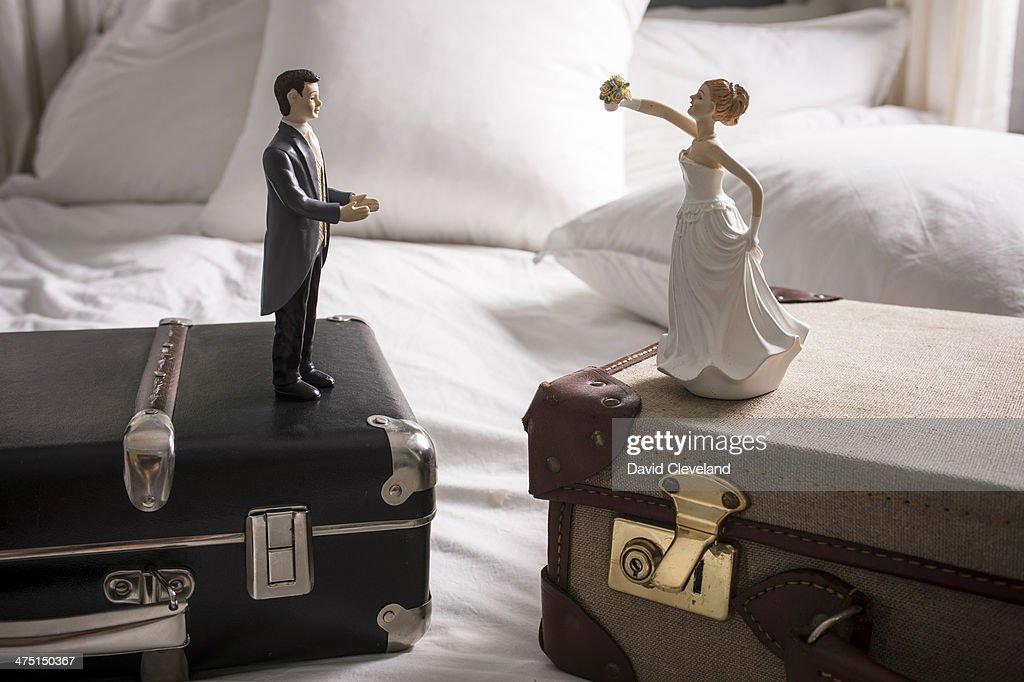 Wedding figurines on separate suitcases : Stock Photo