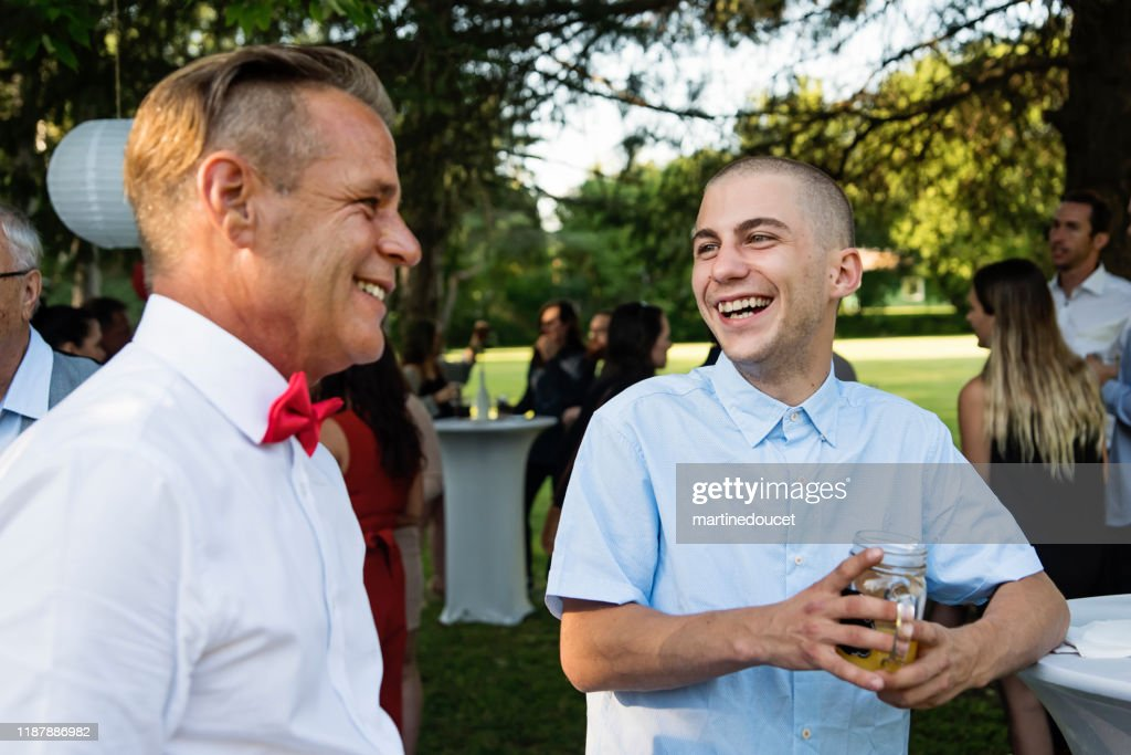 Wedding guests, father and son enjoying themselves at cocktail. : Stock Photo