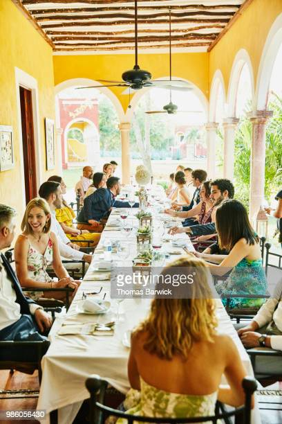 Wedding guests seated at table for dinner during outdoor wedding reception