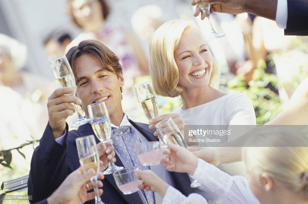 Wedding guests toasting to bride and groom, outdoors : Stock Photo