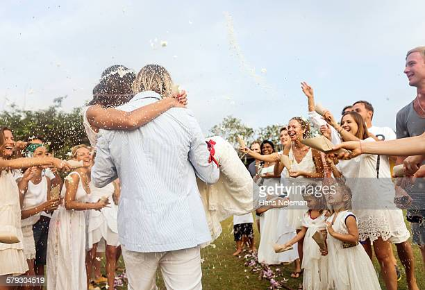Wedding guests tossing rice at newlyweds, outdoors
