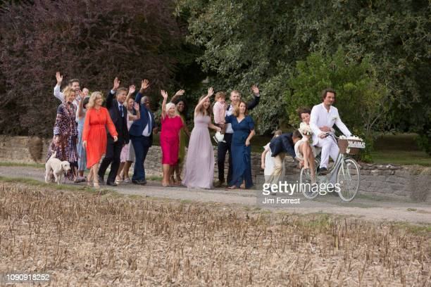 wedding guests waving off newlyweds on bicycles - invité photos et images de collection