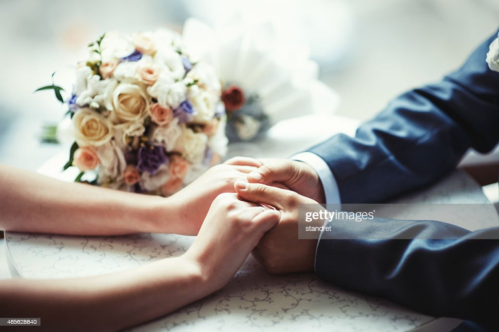 Wedding invitation of a close-up of the couple holding hands : Stock Photo