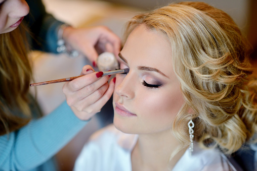 Wedding makeup artist making a make up for bride 528908438
