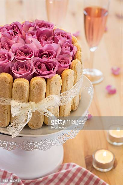 Wedding or birthday cake with fresh lilac rose on wooden table up. Closeup.