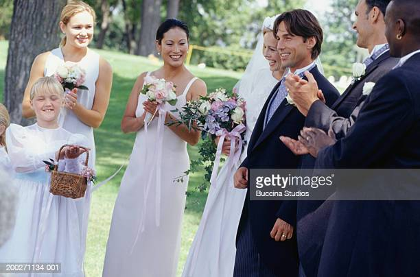Wedding party applauding bride and groom in park