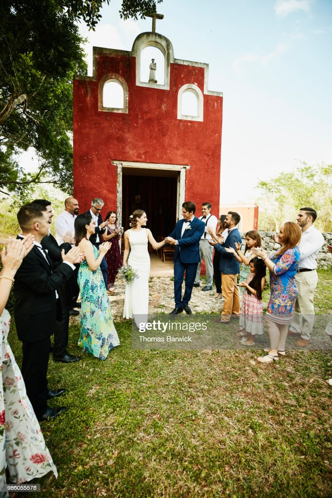 wedding party congratulating bride and groom as they walk down the aisle after outdoor resort wedding