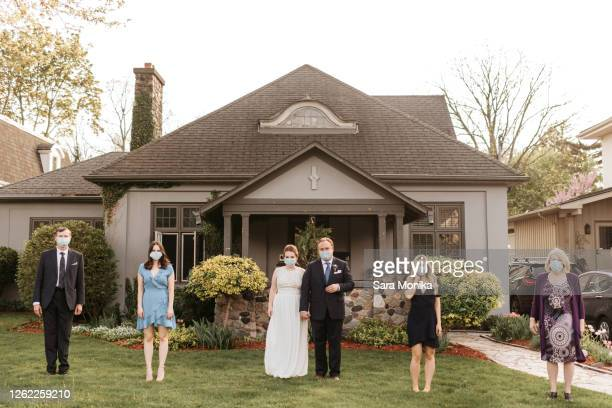 wedding party posing for group portrait on front lawn, wearing face masks during coronavirus crises. - wedding stock pictures, royalty-free photos & images