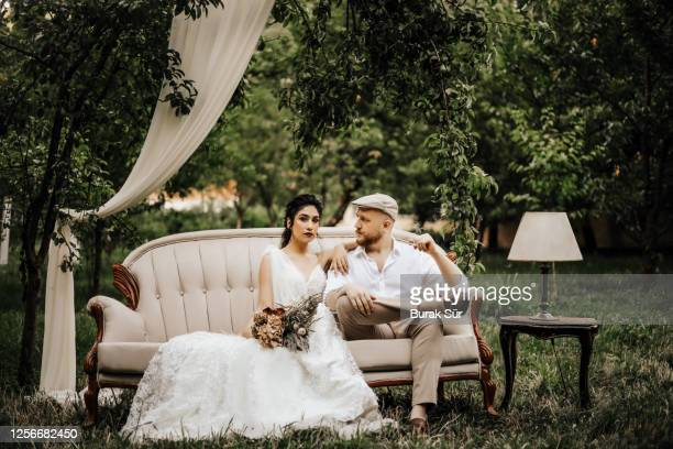 wedding photo, bride and groom sitting on the sofa and posing - wedding stock pictures, royalty-free photos & images