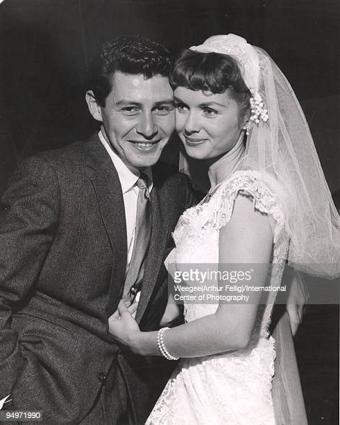 Wedding photo of singer and performer Eddie Fisher with actress Debbie Reynolds wearing wedding gown Grossinger NY 1955 Photo by Weegee/International...