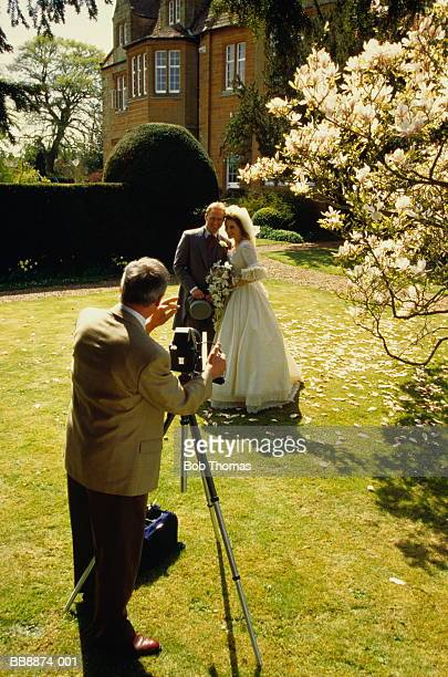 Wedding photographer taking picture of bride and groom