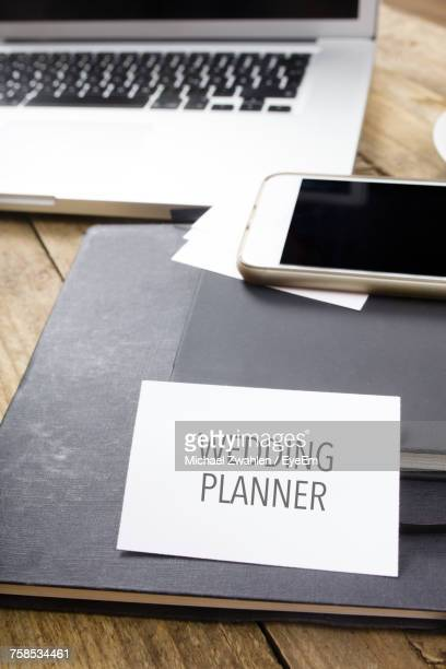 Wedding Planner Text On Paper Over Diary At Desk