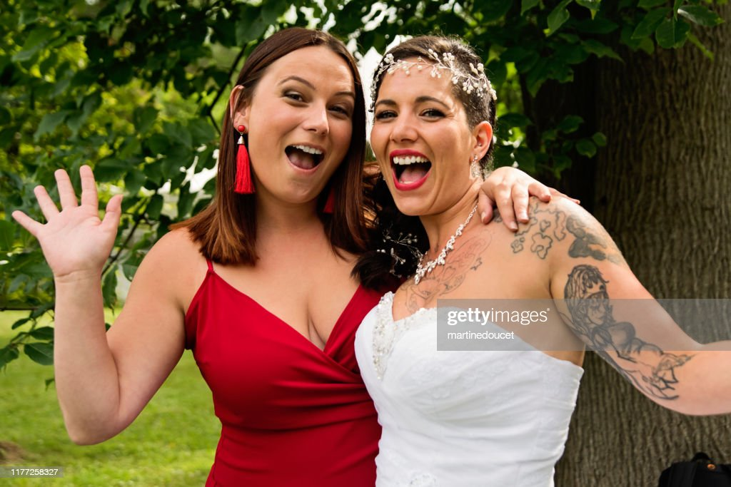 Wedding portrait of millennial bride with bridesmaid outdoors. : Stock Photo