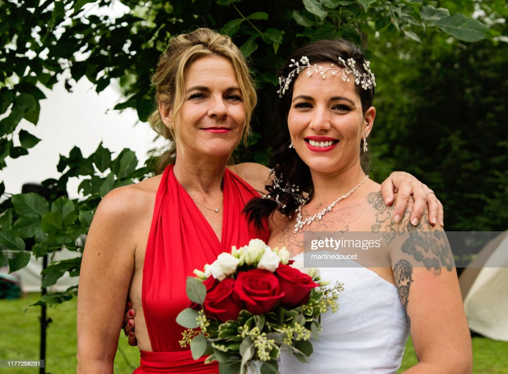Wedding portrait of millennial bride with mother outdoors. : Stock Photo