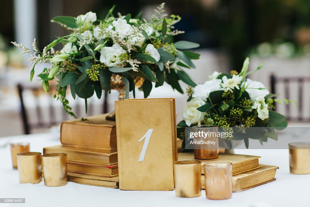 Wedding Reception Table Decor with Gold Accents and Flower Arrangements : Stock Photo