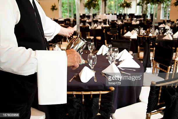 Wedding reception waiter pouring water into glasses. Waitstaff.  Serving.