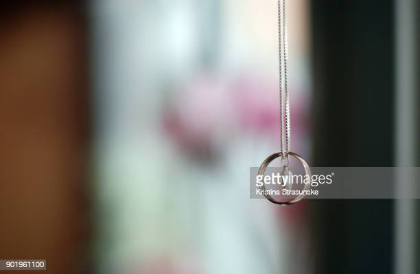 wedding ring hanging on a necklase with a heart pendant