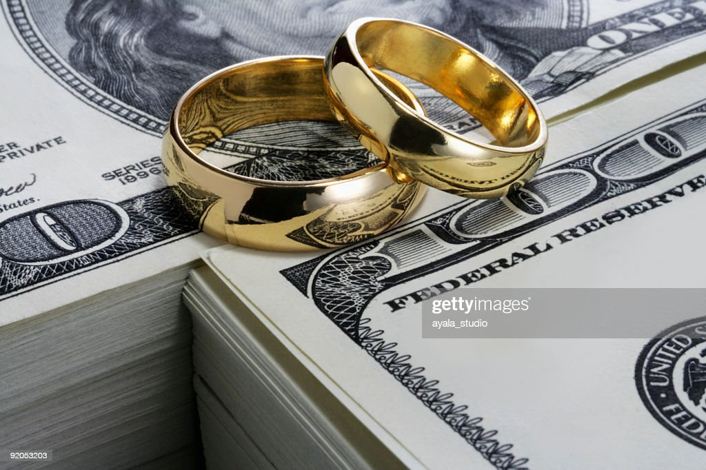Wedding rings and stack of money : Stock Photo