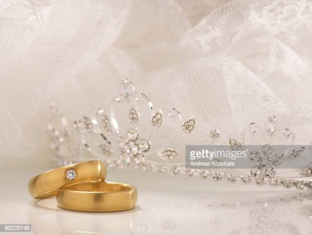 Wedding rings, crown and white lace