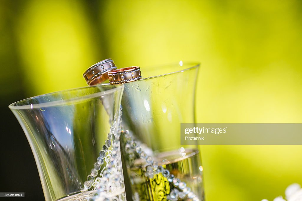 wedding rings lie on champagne glasses : Stock Photo