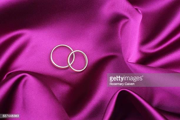 Wedding rings on pink satin sheet