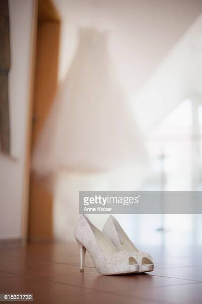 Wedding shoes on the floor with wedding dress in background, Fürstenfeldbruck, Bavaria, Germany