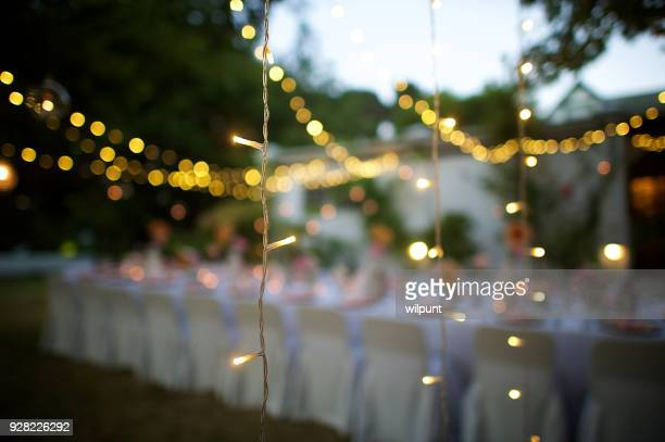 wedding string lights in focus at dusk - outdoor party stock pictures, royalty-free photos & images