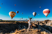 Wedding travel. Honeymoon trip. Couple in love among balloons. A guy proposes to a girl. Couple in love in Cappadocia. Couple in Turkey.  Man and woman traveling. Flying on balloons. Tourists