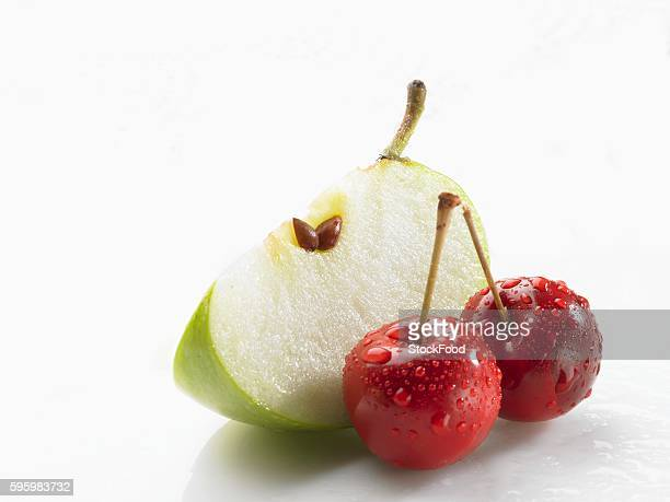 Wedge of green apple and two cherries with drops of water