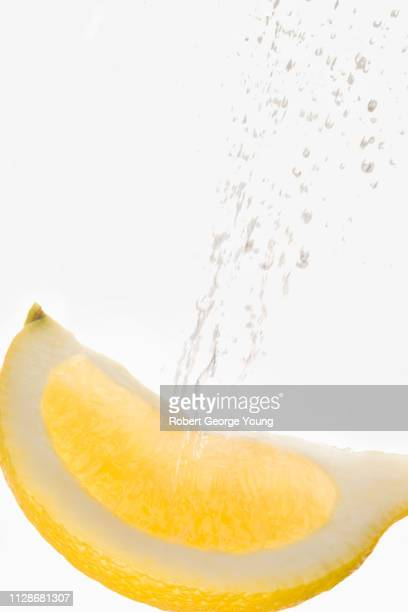 a wedge or slice of lemon squirting juice - squirt foto e immagini stock