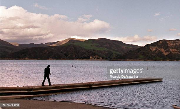 Wednesday, 3/8/2000 –– Fisherman walking on the dock at Lake Piru's launching area in the late afternoon.