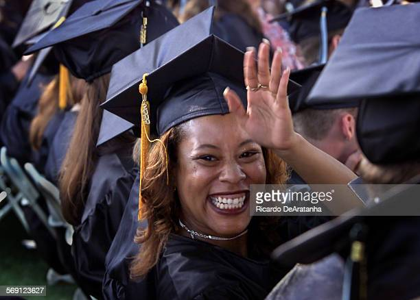 Wednesday 5/11/2000 Moorpark CA –– Dalmeashia Gayton of Simi Valley waving to her family during Moorpark College year 2000 graduation this afternoon