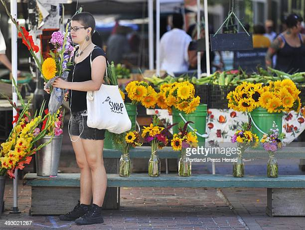 Wednesday August 8 2012 Maria Sedler of Portland shops for flowers at the Farmers Market on Wednesday morning in Portland's Monument Square