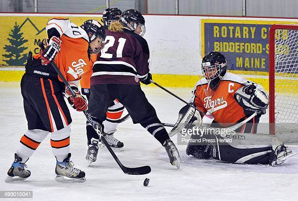 Wednesday December 21 2011 Biddeford Dalani Roy sweeps the puck out of danger after goalie Emily Brassley makes a point blank save on Gorham/Bonny...