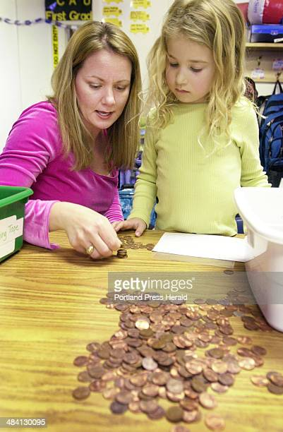 Tracy Armitage helps Anna Burns a firstgrader at Lunt School in Falmouth count pennies that will be donated to Oxfam for tsunami relief Lunt school...