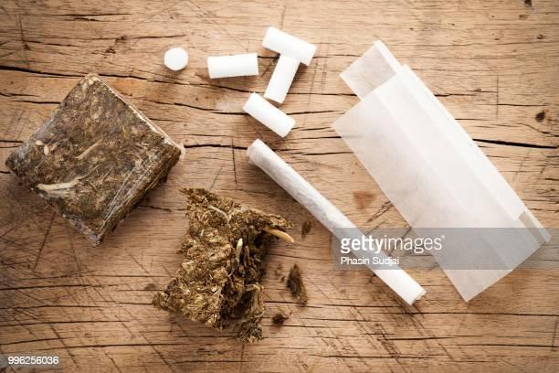 weed marijuana hashish roll wood background - hashish stock pictures, royalty-free photos & images